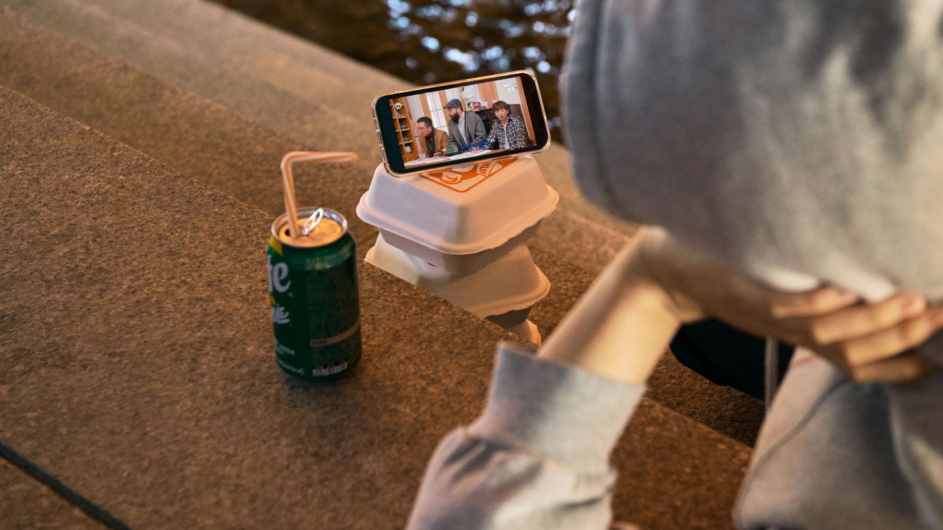 야외에서 간식과 함께 핸드폰으로 카카오TV 통해 영상을 보고 있는 사람의 사진
