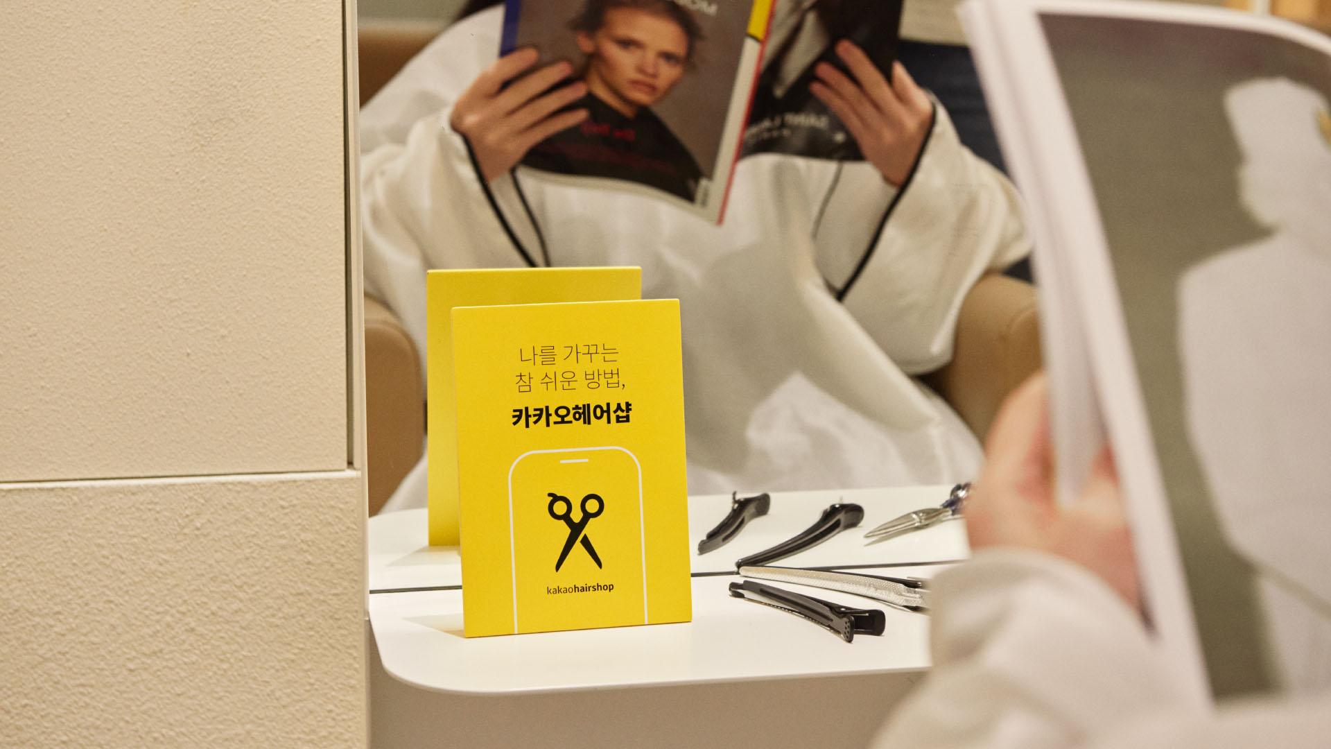 미용실에서 잡지를 읽으며 머리시술을 받고 있는 고객과 카카오헤어샵 제휴 홍보물이 함께 있는 사진
